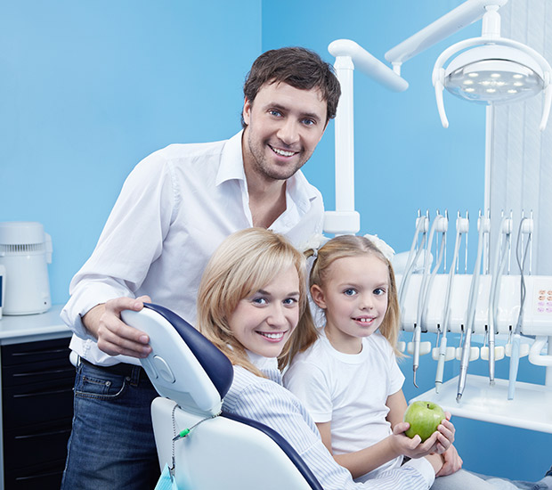 Male dentist smiling with a very young female patient and her mom