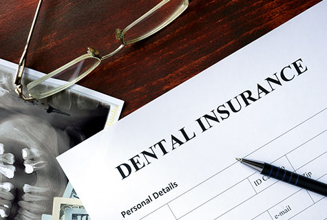 Dental insurance form on a desk with a pen and glasses