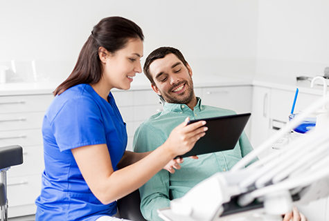 Young female dental assistant smiling as she shows a screen to a smiling male patient
