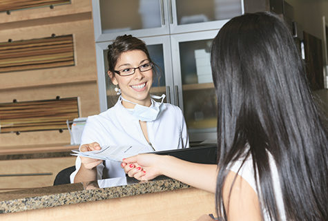 Female staff member exchanging paperwork with a female patient